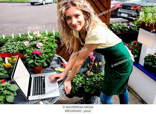 Florist using laptop in garden centre