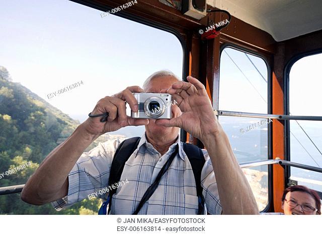 Senior tourist man taking photo from inside of cable car Gibraltar, UK