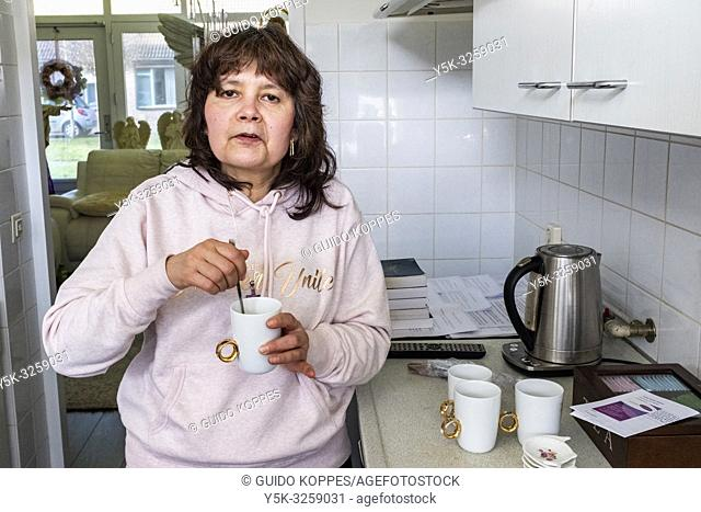 Dongen, Netherlands. Middle aged woman preparing for an alternative spiritual service inside the residential kitchen of her Spiritual Leader