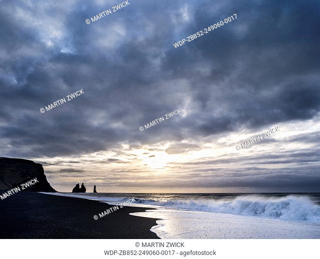 Coast of the North Atlantic near Vik y Myrdal during winter. Beach during sunrise with the sea stacks called Reynisdrangar