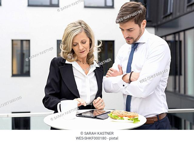 Businessman and businesswoman having lunch break with digital tablet