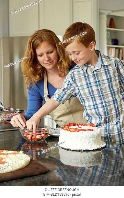 Caucasian mother and son decorating cake in kitchen