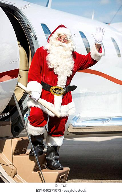 Full length portrait of Santa waving hand while standing on private jet's ladder at airport terminal