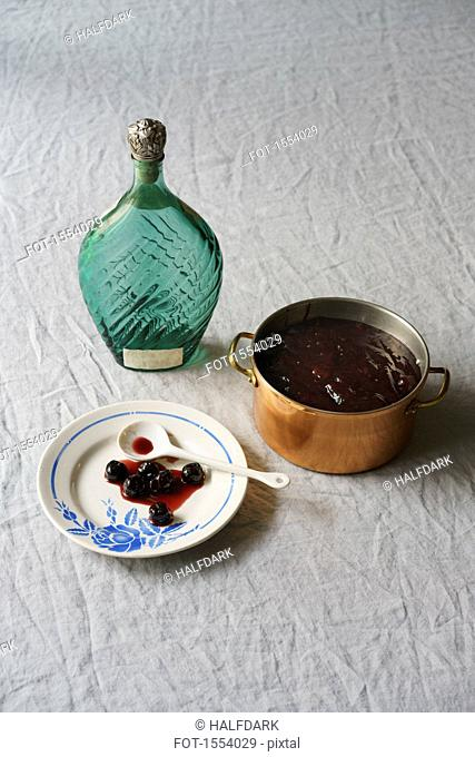 High angle view of blueberry syrup with container and bottle on tablecloth