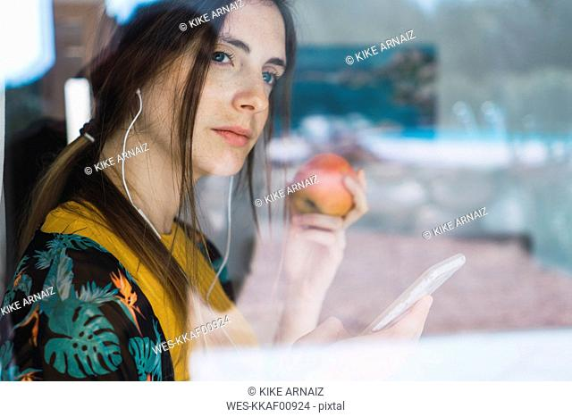Young woman with earphones, cell phone and apple looking out of window