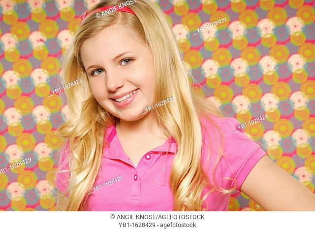 Close up portrait of a smiling ten year old girl with long blond hair, standing in front of a colorful background