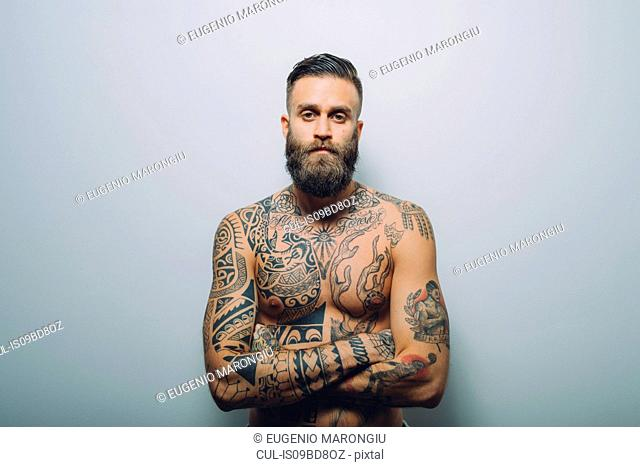 Portrait of young man with beard, bare chest covered in tattoos, arms folded