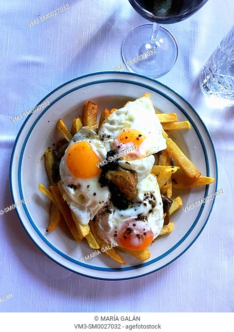 Fried eggs with potatoes and truffle. View from above