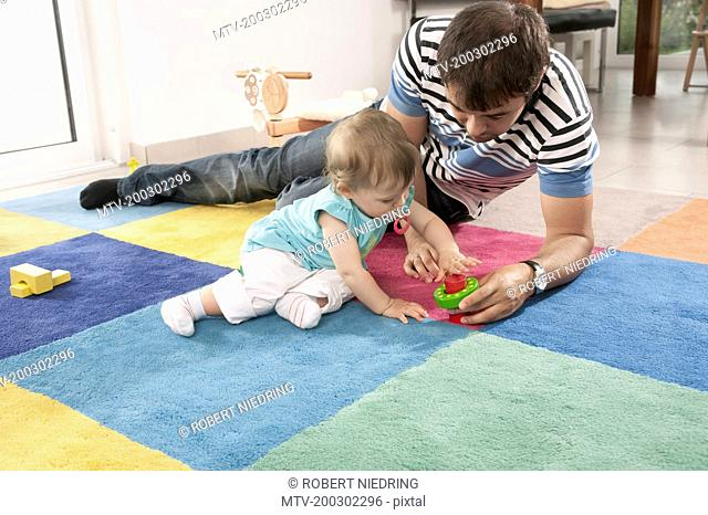 Playing toy father baby girl daughter carpet