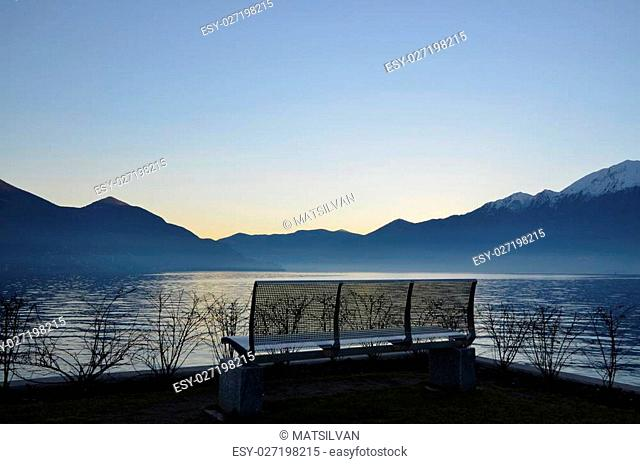 Sunset over an alpine lake with mountains and benches