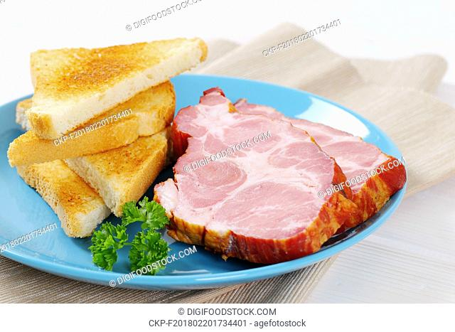 smoked pork with toasted bread on turquoise plate