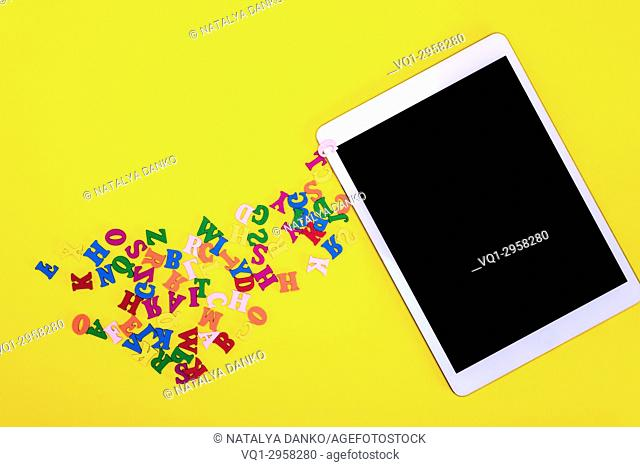 multicolored wooden letters and electronic tablet with a black screen on a yellow background