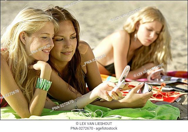 Girls on beach with mobile phone, Scheveningen, the Netherlands