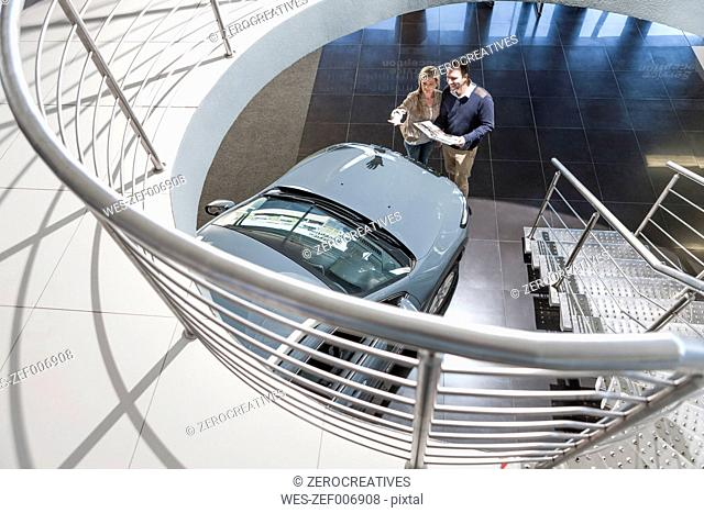 Couple looking at new car in showroom