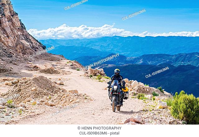 Man driving on touring motorbike on dirt road, Potosi, Bolivia