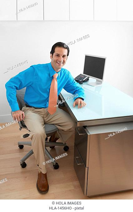 Businessman sitting and smiling in an office