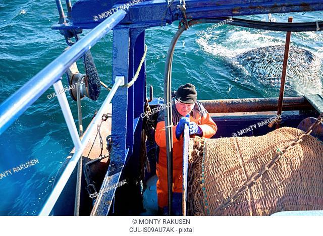 Fisherman bringing in catch on trawler