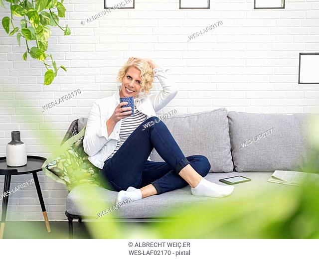 Portrait of smiling mature woman sitting on couch at home holding coffee mug