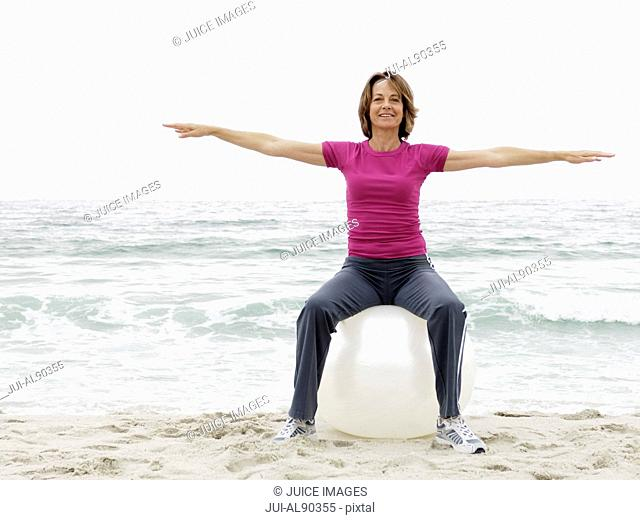 Woman using exercise ball at beach