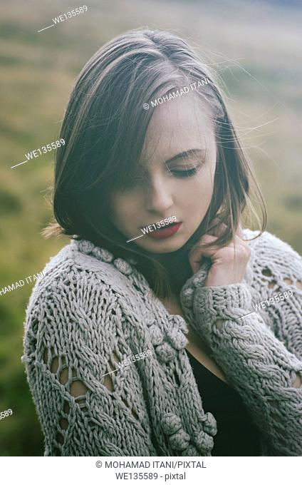 Portrait of a beautiful young woman in wolen cardigan outdoors