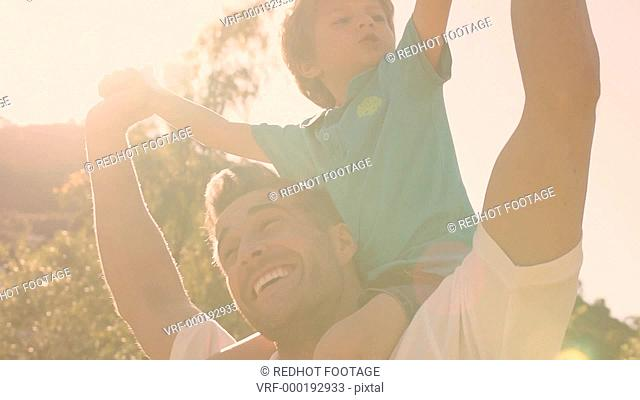 Father with son on shoulders in park