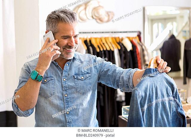 Caucasian man examining shirt talking on cell phone