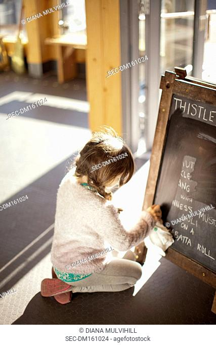 Girl (8-9) kneeling and wiping blackboard