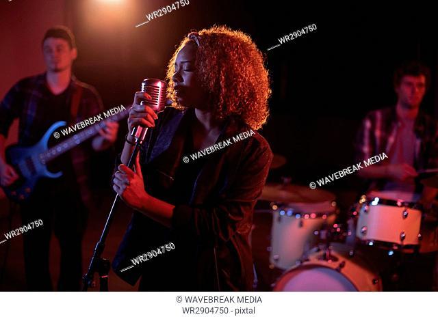 Woman singing on retro microphone