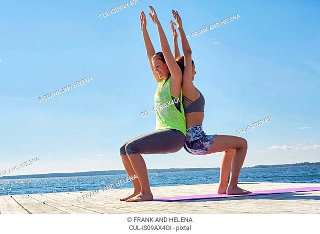 Side view of women on pier squatting back to back arms raised
