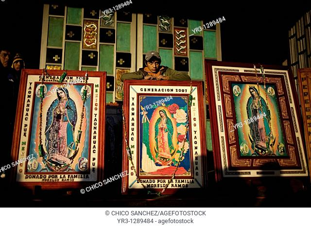 A teenager stands behind images of Our Lady of Guadalupe in Mexico City, December 10, 2010  Hundreds of thousands of Mexican pilgrims converged on the Our Lady...