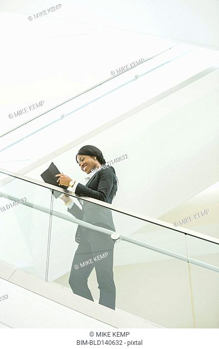 Black businesswoman using digital tablet on office staircase