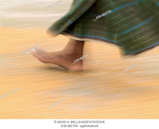 Worker uses his feet as he turns over rice that is drying in a rice processing center on a farm in rural Bangladesh