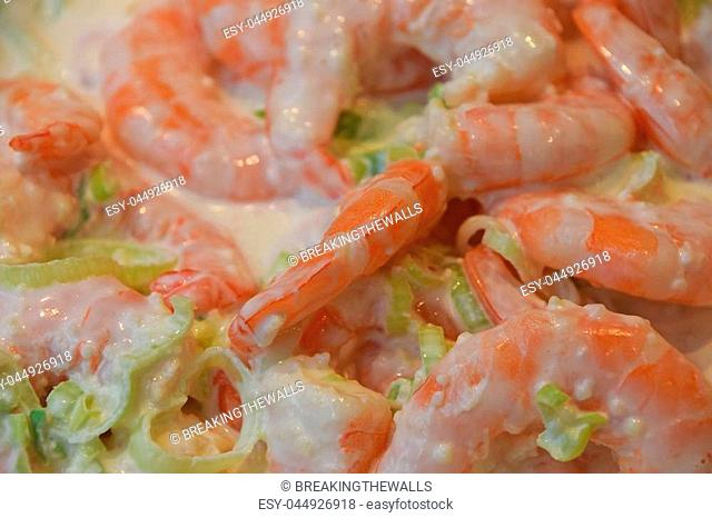 Fresh shrimp cocktail salad with vegetables and white sauce, close up, high angle view, personal perspective