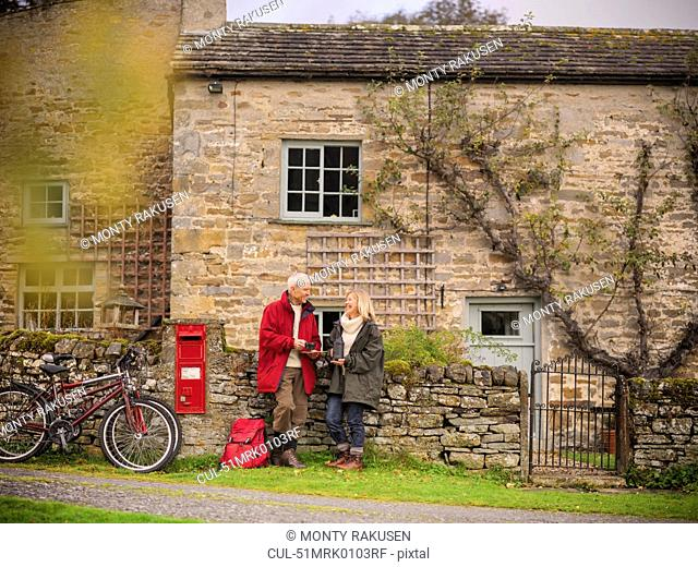 Older couple by stone wall in village