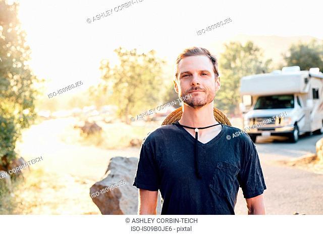 Portrait of man by camper van looking at camera, Malibu Canyon, California, USA