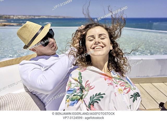 couple on sunbeds, holiday, summer, in Hersonissos, Crete, Greece
