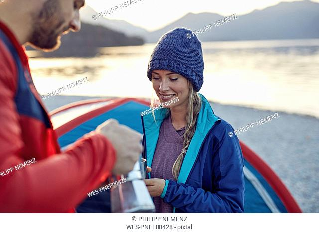Young couple at tent having coffee break