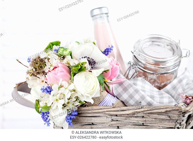 Bouquet from pink tulips, violet grape hyacinths, white anemones, violet veronica and white buttercup with violet ribbon lying in the picnic basket with...