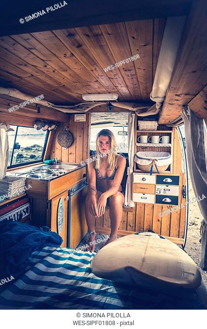 Young woman in bikini sitting in mobile home