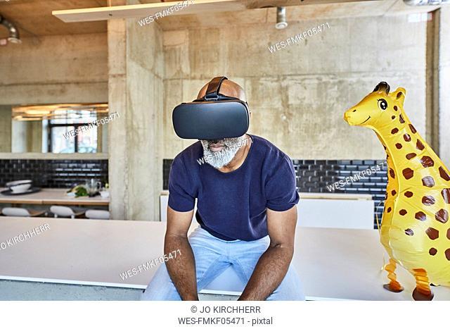 Mature businessman in modern office sitting next to giraffe figurine wearing VR glasses