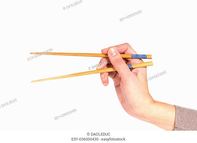 Woman hand holding pair of wooden chopsticks, isolated on white background