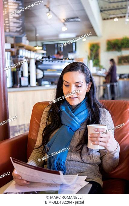 Hispanic woman reading paperwork in cafe