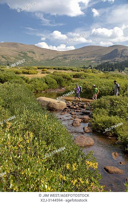 Georgetown, Colorado - Hikers cross a stream on the trail from Guanella Pass to 14,060-foot Mt. Bierstadt in the Mt. Evans Wilderness Area
