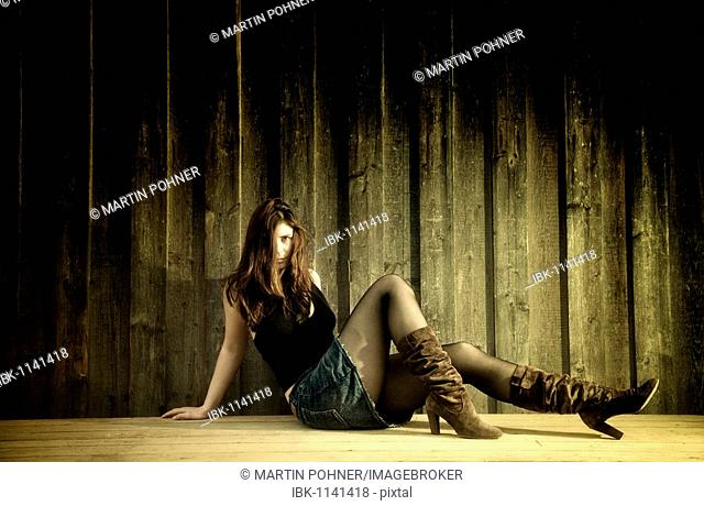Young woman with jeans skirt and boots in front of a wooden wall