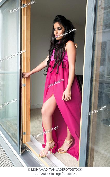 Alluring Indian woman in hot pink dress standing by the baclony door