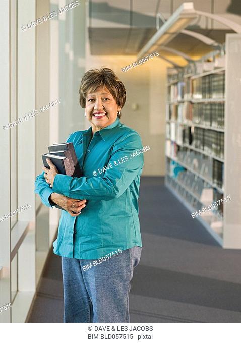 Senior Hispanic woman holding library books