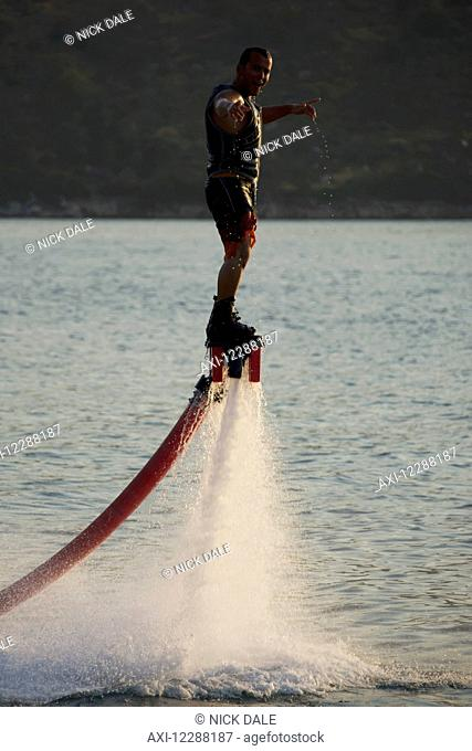 Flyboarder with arms out looking towards camera; Torba, Mugla Province, Turkey