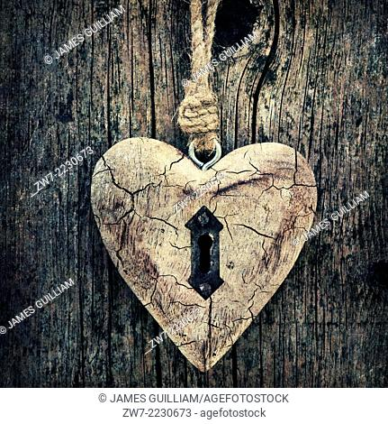 Wooden heart hanging against weathered timber boards