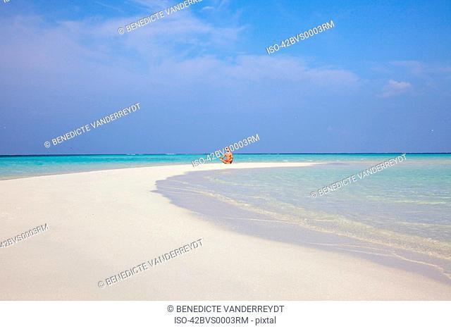 Man meditating on tropical beach