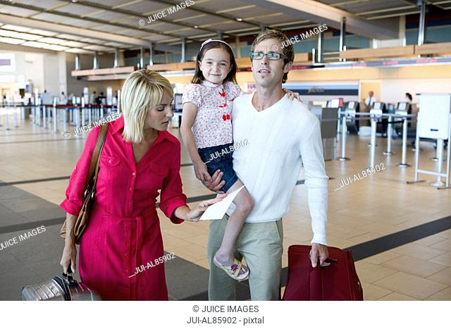 Family looking at ticket in airport